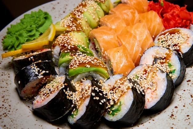 Zestaw sushi z wasabi, imbirem i cytryną na talerzu.