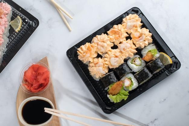 Zestaw sushi z żółtym sosem śmietanowym i krewetkami w pudełkach na wynos