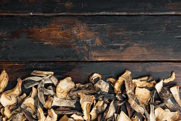 Zestaw suszonych grzybów, na starym ciemnym tle drewnianego stołu, widok z góry płasko leżał, z miejscem na tekst copyspace