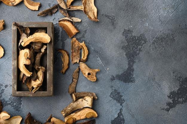 Zestaw suszonych grzybów, na szarym tle, widok z góry płasko leżący, z miejscem na tekst copyspace