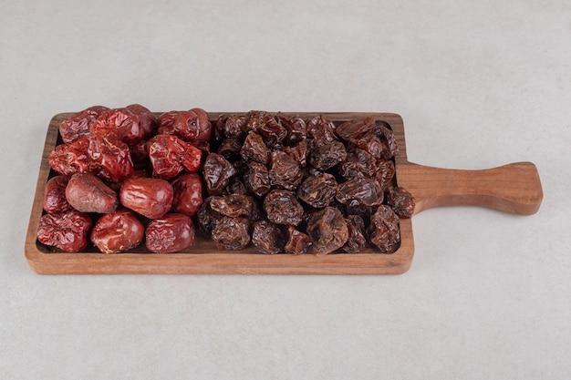 Zestaw suszonych owoców na drewnianym talerzu.