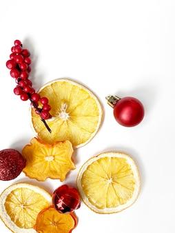 Zestaw suszonych plasterków i pół plasterka pomarańczy i cytryny, na białym tle z dekoracją świąteczną.