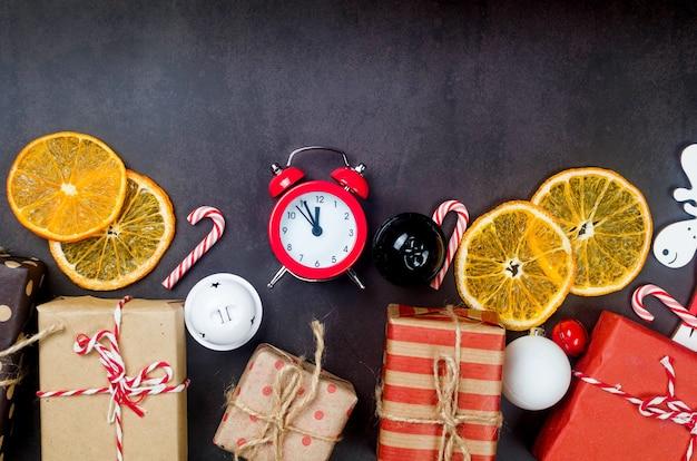 Zestaw świąteczny z prezentami zawiniętymi w papier rzemieślniczy, drewniane zabawki na choinkę, alarm, suche pomarańcze na ciemnym tle. kompozycja sylwestrowa lub zimowa. koncepcja czasu bożego narodzenia. kartka z życzeniami,