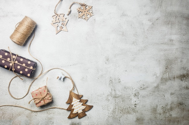 Zestaw świąteczny z prezentami zawiniętymi w papier rzemieślniczy, słodkie drewniane zabawki na choinkę, dekoracje na jasnoszarym tle. kompozycja sylwestrowa lub zimowa. koncepcja czasu bożego narodzenia. kartka z życzeniami,