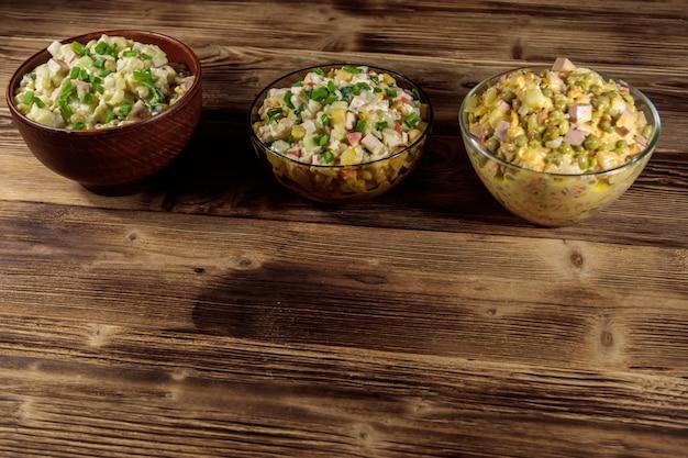 Zestaw świątecznych sałatek majonezowych na drewnianym stole. widok z góry
