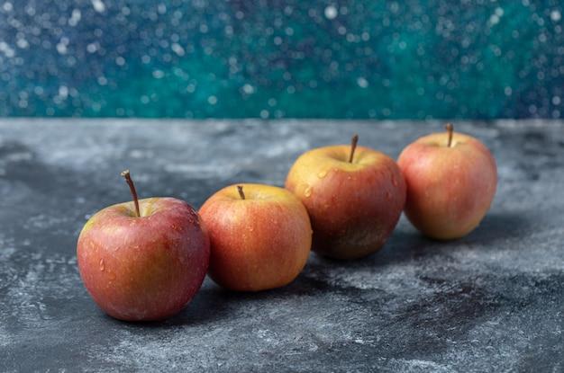 Zestaw świeżego czerwonego żółtego jabłka na marmurowym tle.