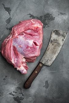 Zestaw świeżego mięsa wieprzowego, ze starym nożem rzeźniczym, na szarym tle kamiennego stołu, widok z góry płaski