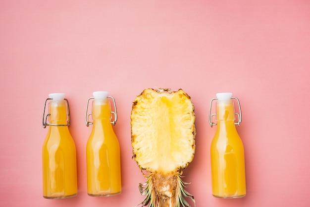 Zestaw świeżego soku ananasowego, na różowym teksturowanym letnim tle, płaski widok z góry, z miejscem na kopię tekstu