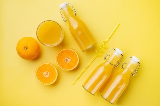 Zestaw świeżego soku pomarańczowego, na żółtym tle z teksturą, widok z góry płaski lay