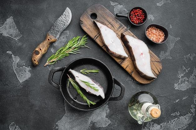 Zestaw świeżego stek z surowej ryby halibuta, ze składnikami i ziołami rozmarynu, na czarnym tle ciemnego kamiennego stołu, widok z góry płasko leżący