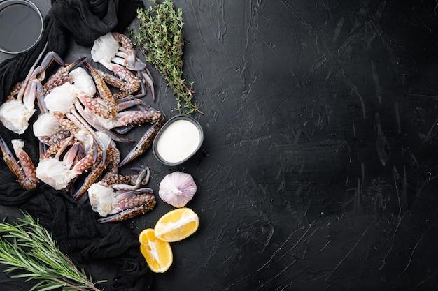 Zestaw świeżego surowego niebieskiego kraba pływackiego oceanu dla smakoszy, na czarnym tle, widok z góry płasko leżący, z copyspace i miejscem na tekst