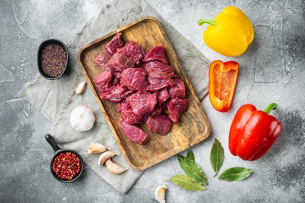 Zestaw świeżej siekanej surowej wołowiny ze słodką papryką, na szarym kamiennym stole, widok z góry na płasko