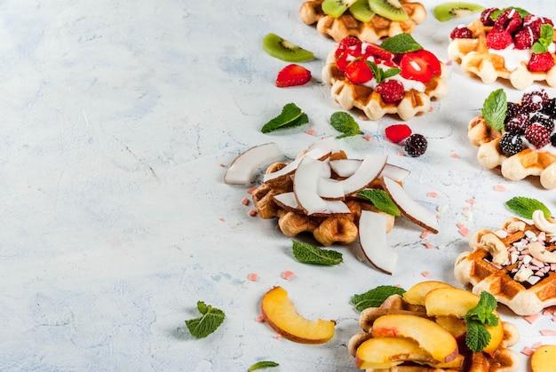 Zestaw świeżych belgijskich miękkich wafli z różnymi dodatkami - brzoskwinia, jeżyny, maliny, truskawki, kokos, orzechy nerkowca, truskawki, mięta. lekki stół. miejsce kopiowania