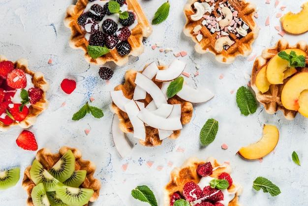Zestaw świeżych belgijskich miękkich wafli z różnymi dodatkami - brzoskwinia, jeżyny, maliny, truskawki, kokos, orzechy nerkowca, truskawki, mięta. lekki stół. widok z góry