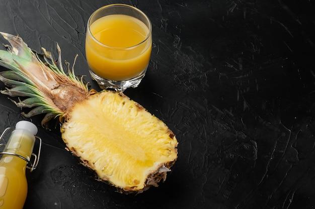 Zestaw świeżych dojrzałych ananasów i szklanka soku, na tle czarnego ciemnego kamiennego stołu, z miejscem na kopię tekstu