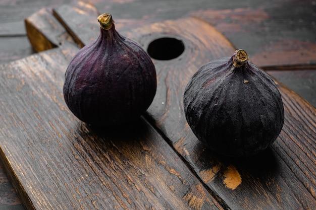 Zestaw świeżych dojrzałych fig, na starym ciemnym tle drewnianego stołu