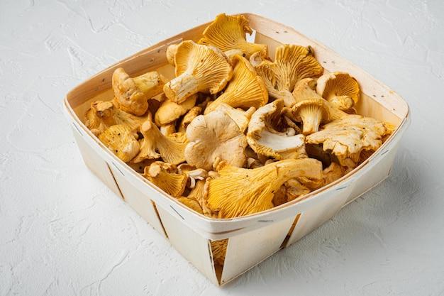 Zestaw świeżych kurek, w drewnianym pudełku, na białym tle kamiennego stołu