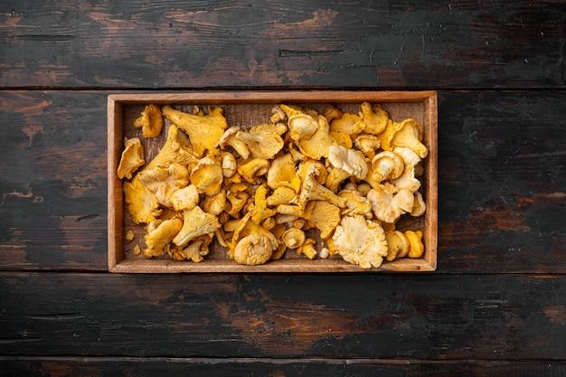Zestaw świeżych kurek, w drewnianym pudełku, na starym ciemnym drewnianym stole, widok z góry płaski lay