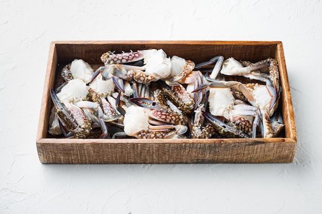 Zestaw świeżych niebieskich części kraba pływackiego, w drewnianym pudełku, na białym tle