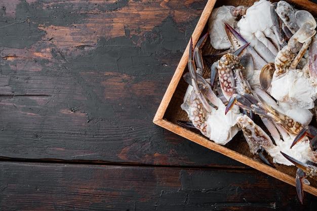 Zestaw świeżych surowych kwiatów krabów lub krabów niebieskich, w drewnianym pudełku, na ciemnym drewnianym tle, z copyspace i miejscem na tekst