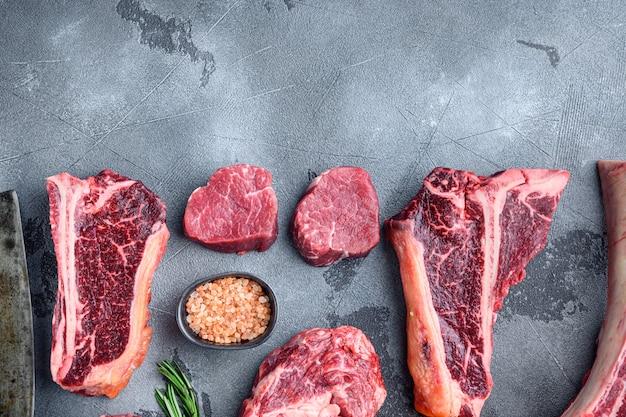 Zestaw świeżych, surowych marmurkowych steków wołowych, tomahawk, kości t, stek klubowy, żeberka i kawałki polędwicy, na szarym kamiennym stole, widok z góry na płasko