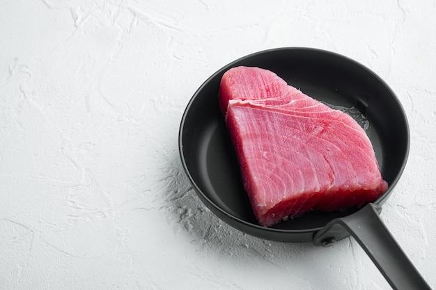 Zestaw świeżych surowych steków z tuńczyka, na patelni żeliwnej, na białym tle kamienia, z copyspace i miejscem na tekst