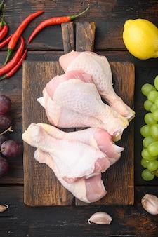 Zestaw świeżych udek z kurczaka i składników marynaty, na drewnianej desce do krojenia, na starym ciemnym drewnianym stole, widok z góry na płasko