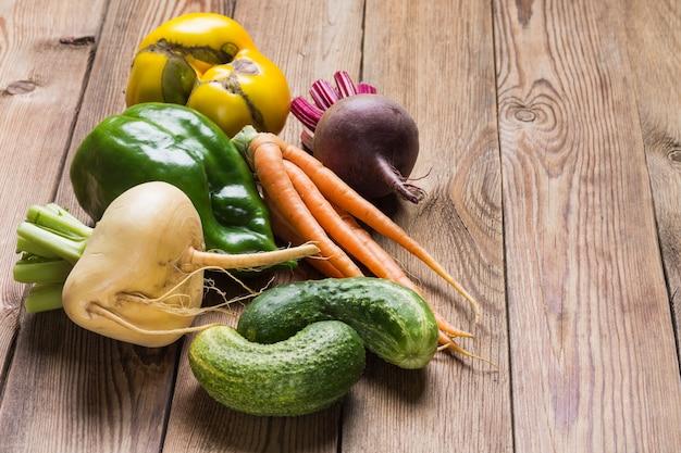 Zestaw świeżych warzyw (burak, pomidor, rzepa, zielona papryka, ogórek) na drewnianym stole.