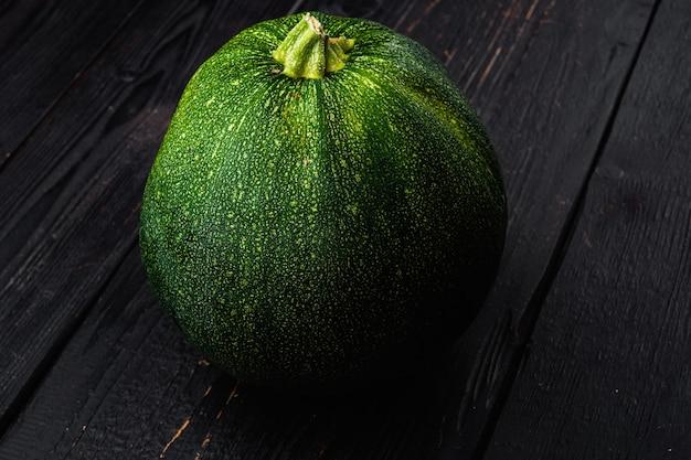 Zestaw świeżych warzyw cukinii, na czarnym tle drewnianego stołu