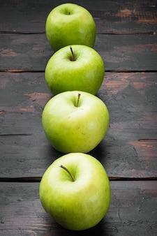 Zestaw świeżych zielonych jabłek, na starym ciemnym tle rustykalnym stołu