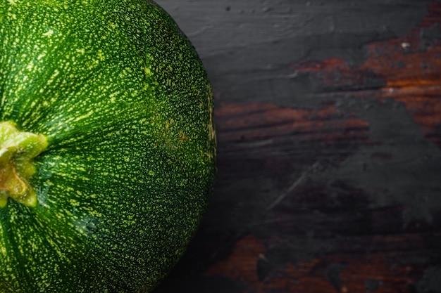 Zestaw świeżych zielonych kabaczków, na starym ciemnym tle drewnianego stołu, płaski widok z góry, z miejscem na kopię tekstu