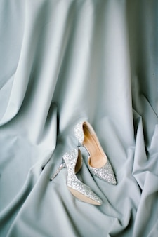 Zestaw szare tkaniny i obcasy i dekoracje ślubne na szarym tle z teksturą. widok z góry.