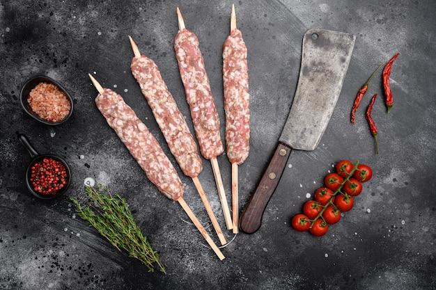 Zestaw szaszłyków z surowego kebabu z baraniny, ze składnikami grilla, na czarnym tle ciemnego kamiennego stołu, widok z góry płasko leżący