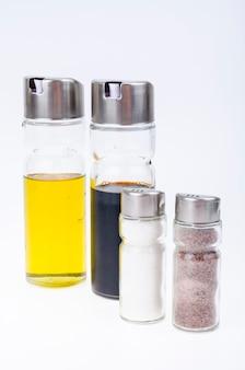 Zestaw szklanych butelek z oliwą z oliwek, octem, solą i pieprzem do nakrycia stołu