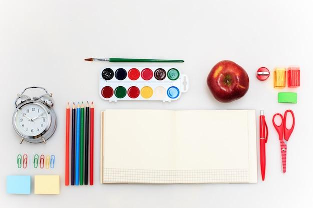 Zestaw szkolny z zeszytami, ołówkami, pędzlem, nożyczkami i jabłkiem na białym tle