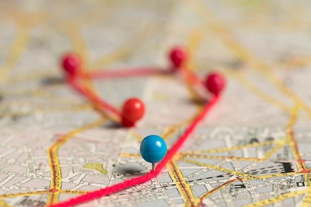 Zestaw szpilek i nici piśmiennych na widoku mapy wysokiej