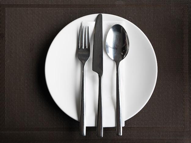 Zestaw sztućców nóż widelec i łyżka na białym talerzu.