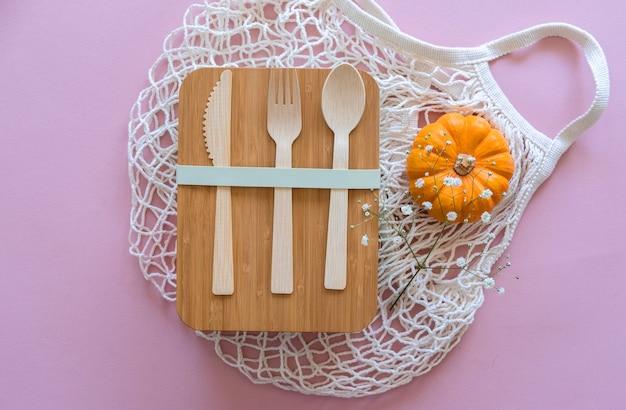 Zestaw sztućców (widelec, łyżka, nóż) wykonany z drewna lub bambusa, bambusowy pojemnik na lunch wielokrotnego użytku oraz bawełniana siatka na zakupy. koncepcja zero waste.