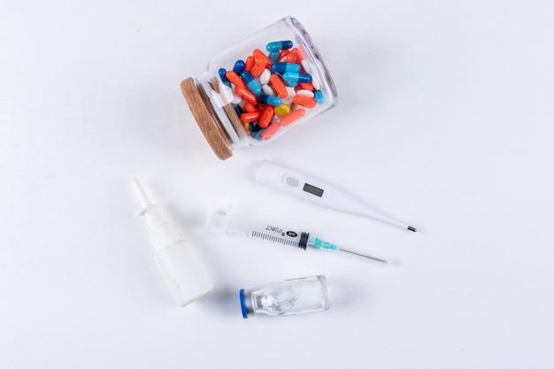 Zestaw termometru, aerozolu do nosa, igły i tabletek w słoiku