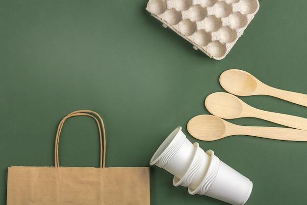 Zestaw torby ekologicznej, biodegradowalnych papierowych kubków do kawy, pudełka na jajka z tektury, drewnianych łyżek i szklanej butelki z wodą. zero odpadów, przyjazne dla środowiska, bez plastiku. widok z góry, lato.
