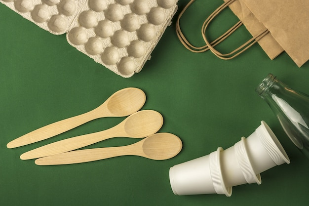 Zestaw torby ekologicznej, biodegradowalnych papierowych kubków do kawy, pudełka na jajka z tektury, drewnianych łyżek i szklanej butelki z wodą. zero odpadów, przyjazne dla środowiska, bez plastiku.