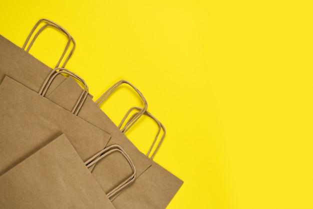 Zestaw toreb papierowych do robienia zakupów na żółtym stole.