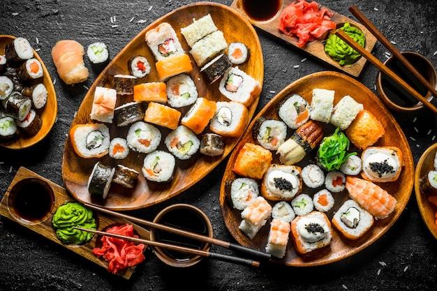 Zestaw tradycyjnego japońskiego sushi z sosem sojowym i imbirem. na czarnej powierzchni rustykalnej