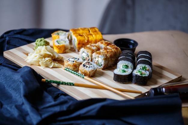 Zestaw tradycyjnych japońskich potraw na ciemnym tle. roladki sushi, nigiri, stek z surowego łososia, ryż, serek, awokado, limonka, marynowany imbir. rama kuchni azjatyckiej.