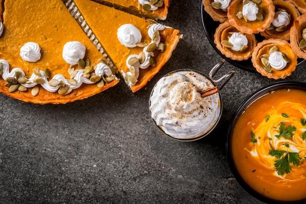 Zestaw tradycyjnych jesiennych potraw. halloween, święto dziękczynienia. pikantna latte z dyni, ciasto z dyni i tartalety z bitą śmietaną i pestkami dyni, zupa dyniowa, na czarnym kamiennym stole. widok z góry