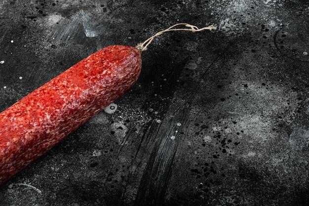 Zestaw tradycyjnych wędzonych kiełbas salami, na czarnym ciemnym kamiennym stole