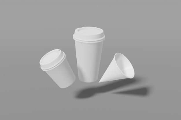 Zestaw trzech białych kubków papierowych o różnych rozmiarach na szarym tle