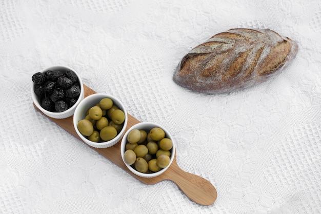 Zestaw trzech białych misek z oliwkami na drewnianej tacy na białym kocu