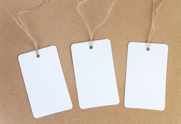 Zestaw trzech pustych etykiet z białego papieru lub metki na brązowym tle