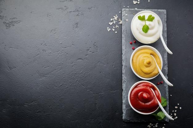 Zestaw trzech sosów - majonezu, musztardy i keczupu w białych ceramicznych miseczkach na czarnym kamieniu lub betonie.